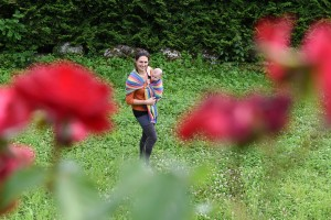 Low angle shot Behind red flowers blurred a mommy holding her young baby with a scarf
