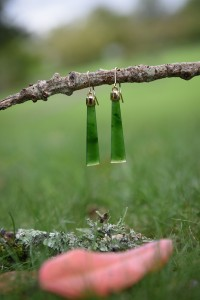 On a little branch greenstone earrings dangling with a blurred red leaf
