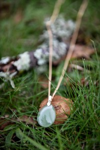 On the grass a greenstone necklace putting down a little mushroom