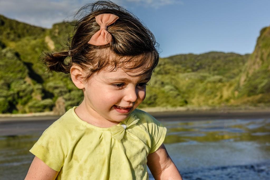 Ainoha laughing and splashing around on NZ beach