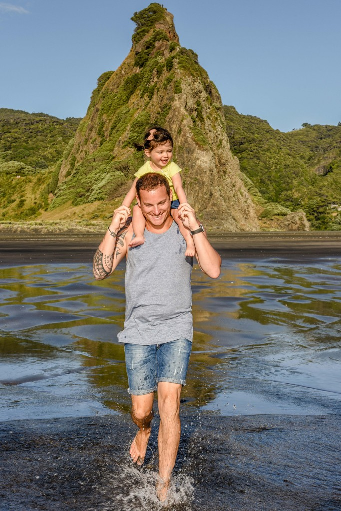 Father carries daughter on shoulders on the beach.