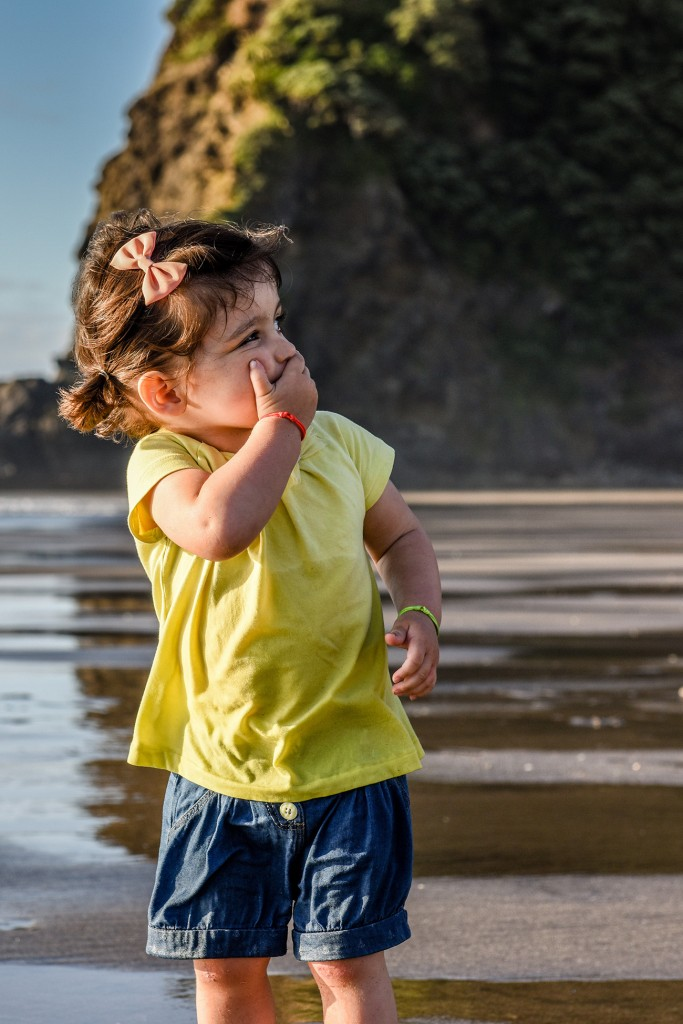 Young girl spots something and gasps on the beach