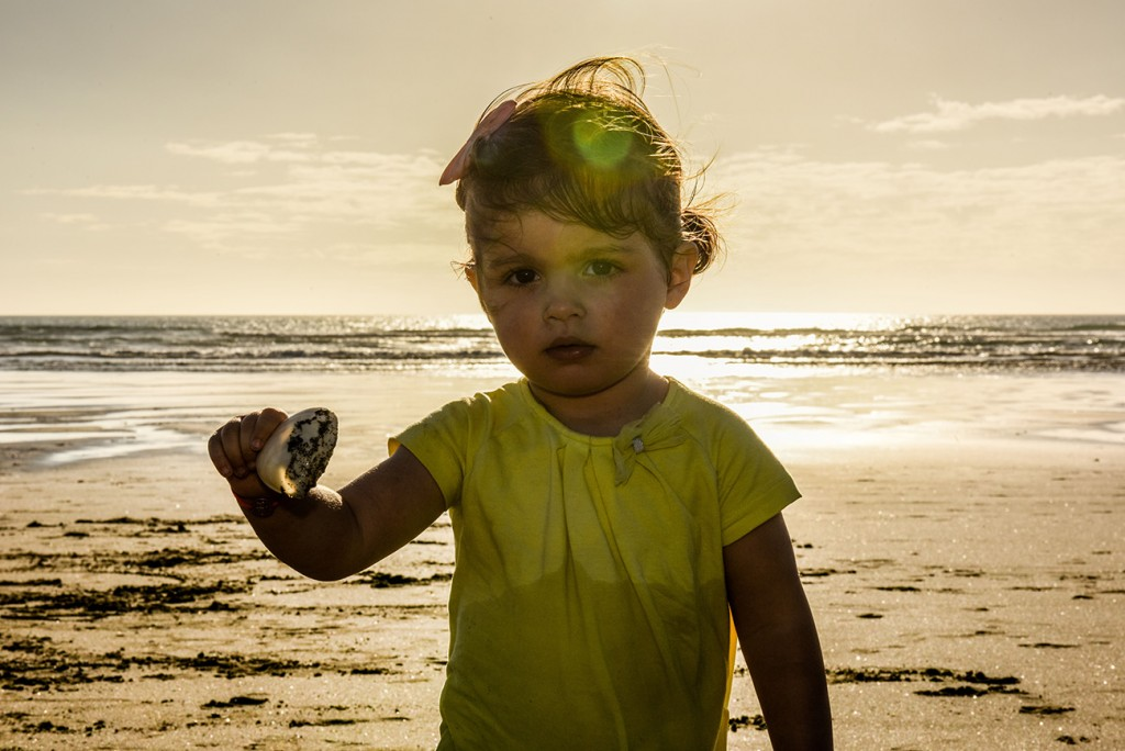 Silhouette of young girl during sunset at NZ beach with Bokeh