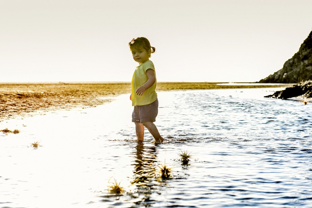 Young girl walks in water on NZ beach