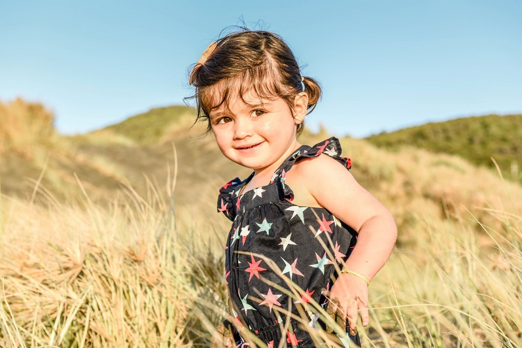 Young girl playing in grass in NZ park