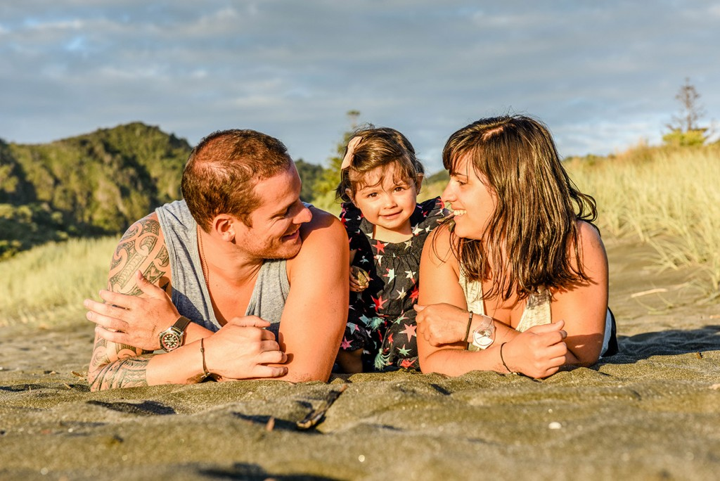 Family pause for camera on NZ beach at sunset