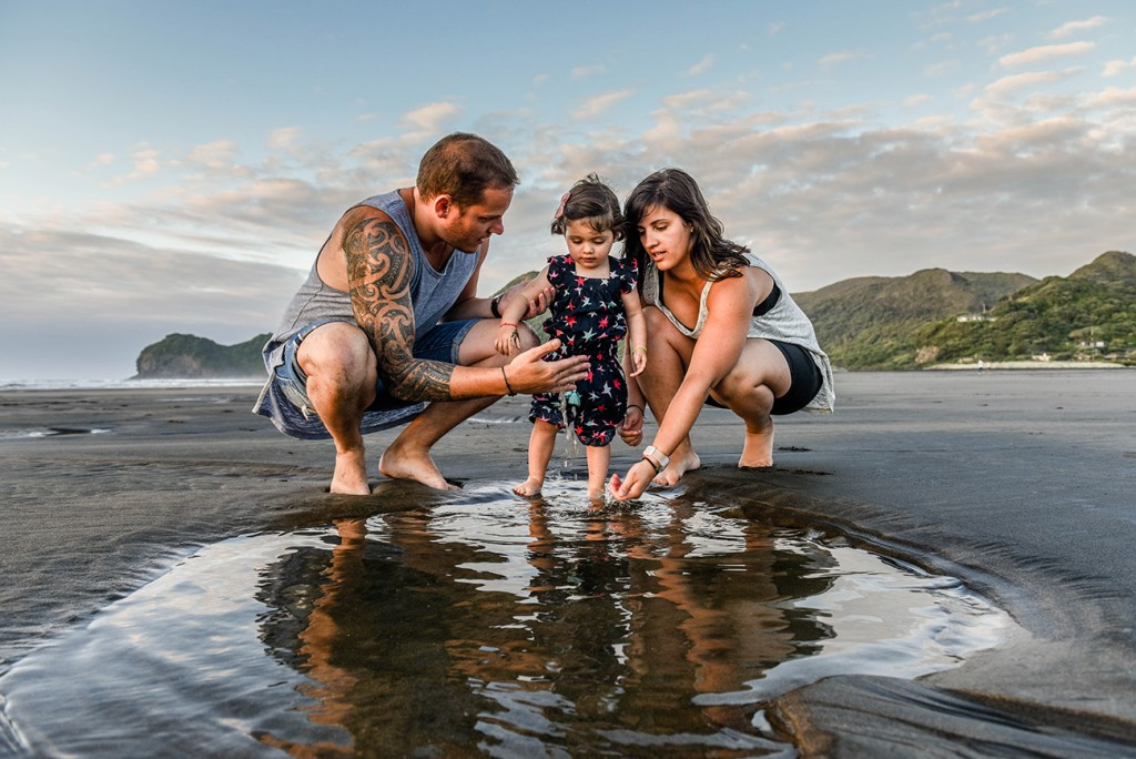 Family plays in puddle on NZ beach