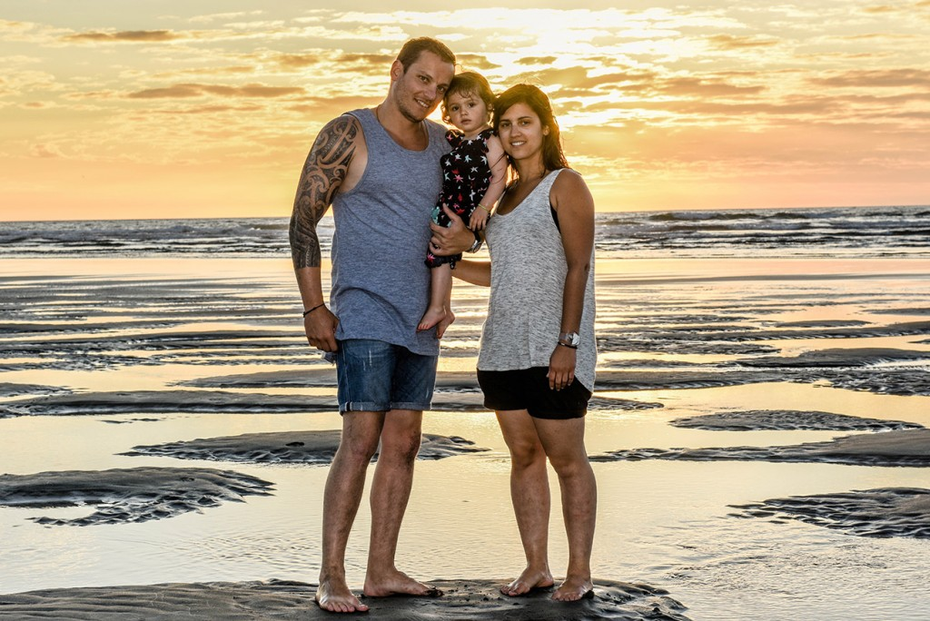 Family pause on NZ beach at sunset