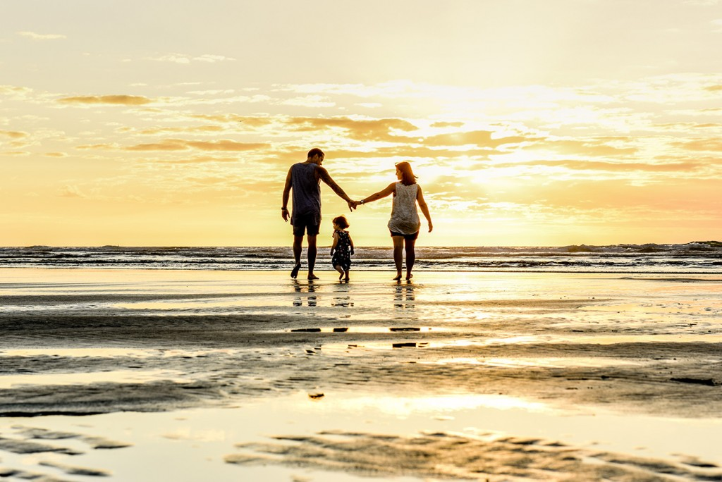 Family casts silhouette as they walk into sea on NZ beach at sunset