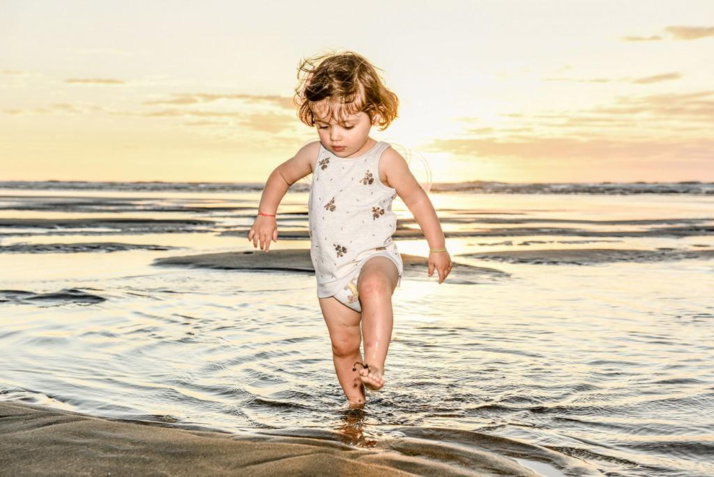 Baby girl splashing in water on NZ beach at sunset