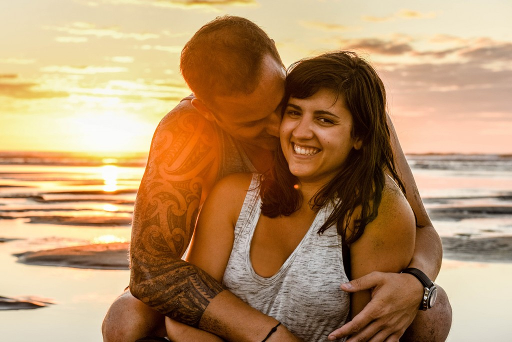 Husband and wife cuddle at an NZ beach with sunset in background