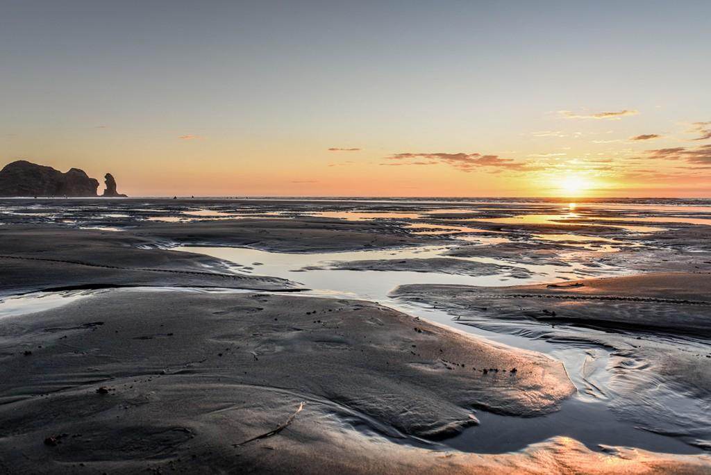 Stunning sunset on Piha black sand beach