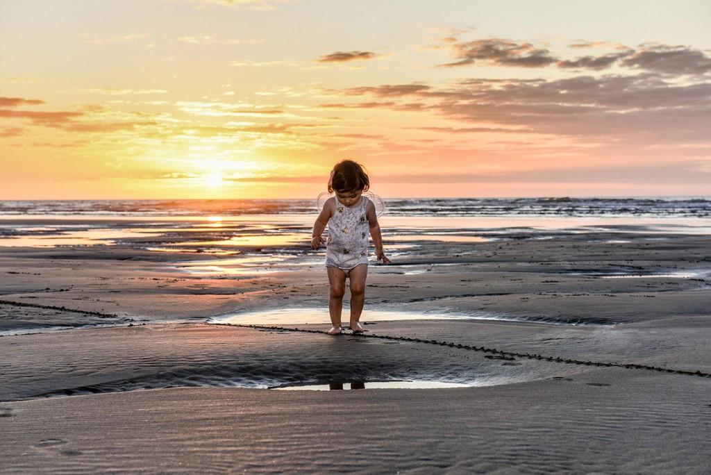 Light silhouette of baby Ainoha on Piha beach NZ at sunset