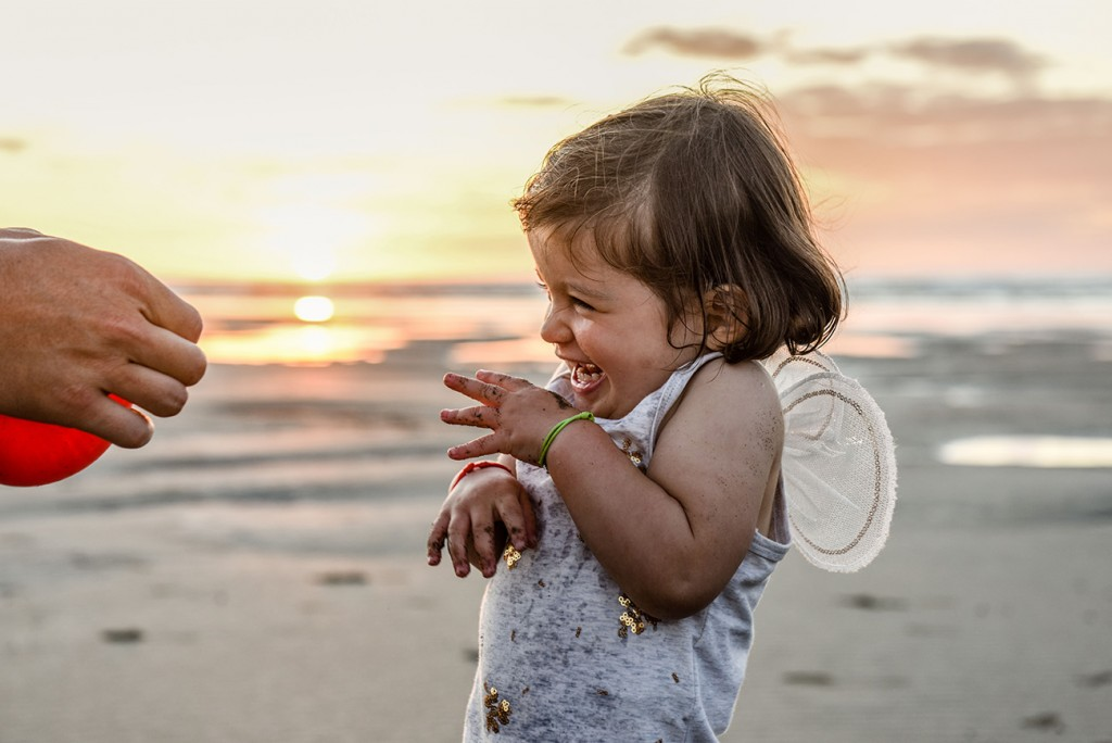 Baby Ainoha giggling in her tiny angel wings, at sunset