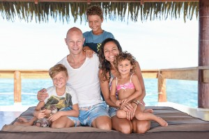 This beautiful family smiles at the camera against the turquoise blue sea aboard Cloud 9 Fiji