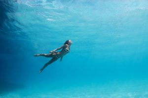 Woman swimming underwater in the pacific ocean