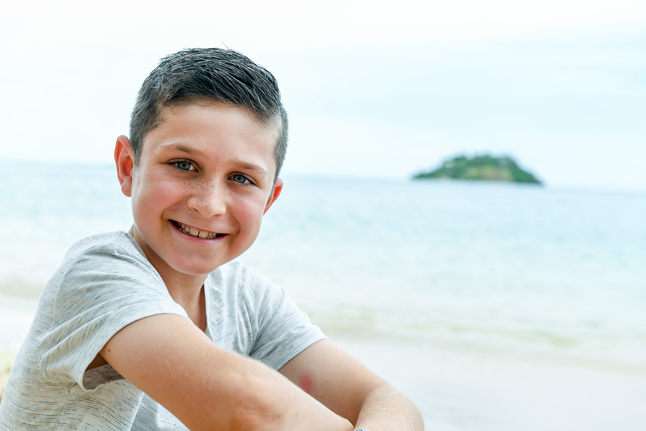Cute boy smiles at the beach in Malolo Island Resort Fiji