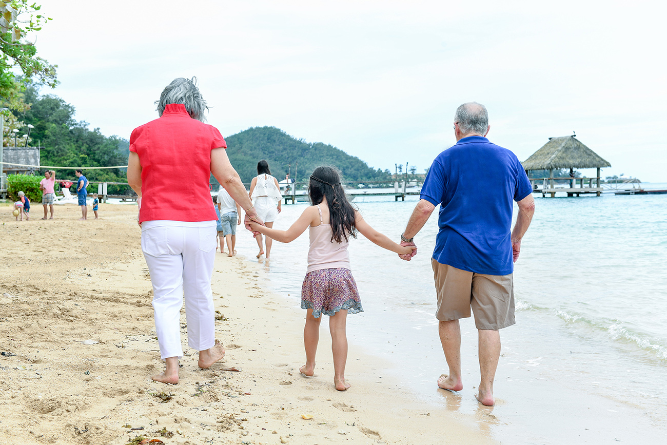 Grandma, grandpa and granddaughter on the shore in Malolo Island Resort Fiji