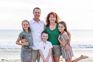 Mum dad and with daughters and son in family photoshoot on the beach