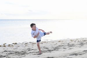 Young boy does karate kick on the beach in Fiji