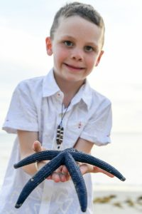 Young boy holds live dark blue starfish in family photoshoot