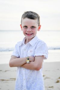 Cute young boy smiles at the camera in beach family photoshoot