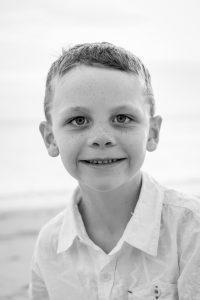 Black and white picture of young boy on the beach