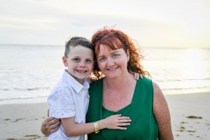 Red haired mum pauses with son on beach in Fiji