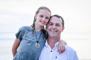 Braided daughter hugs father's shoulder in Fiji