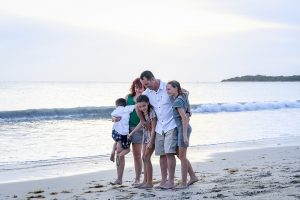 Wideshot of family hugging and cuddling on the beach in Fiji family photoshoot