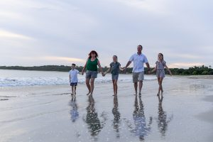 Cute family hold hands as they walk on the beach against Fiji ocean and sunset