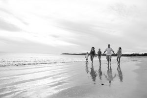 Black and white photo of family walking on the beach in Natadola Fiji