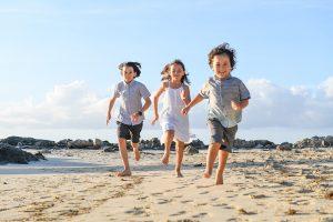 3 cute siblings running on Fiji sandy beach in Malolo village