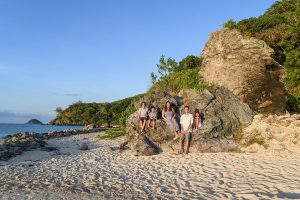Wideshot of family seated on large boulder in family photo session in Fiji
