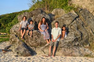 Wideshot of family seated on huge boulder posing at family photo session in Fiji