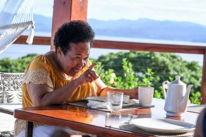 Stern Polynesian grandma points finger n breakfast table