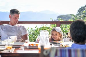 Cute mixed Polynesian girl sends cheeky smile across the table