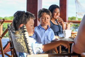 Triplet boys make fun with their toast at the breakfast table in Fiji