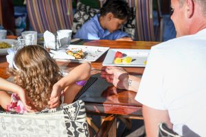 Young triplet girl stretches at the table during breakfast