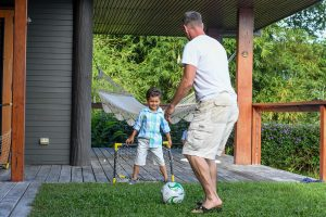 Dad and son play soccer during Fiji family location