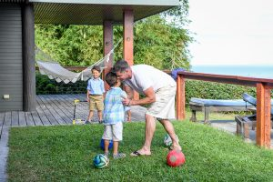 Dad hugs son while playing soccer at Fiji family vacation