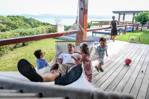 Children swing dad on hammock during Fiji family vacation