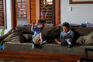 Triplet boys seated on couch indoors during family vacation in Fiji