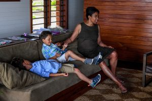 Mom and sons sit on couch in Fiji family vacation