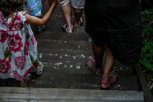 Family feet as they walk on bridge toward tropical rainforest