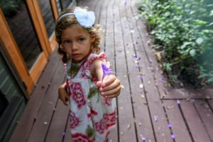Cute little girl with flower in her hair offers camera a purple flower