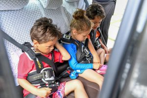 Triplets straddled in car seats durin family drive