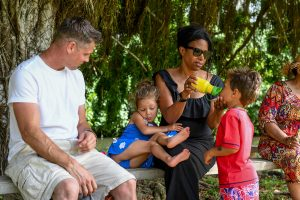 Family sit on park bench in Fiji family vacation