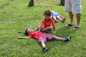 Cute Triplets play in grass during Fiji family vacation