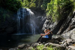 Mother and daughter seated by the river watching waterfall in Fiji